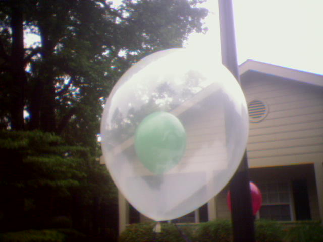 A cellphone photo of a small green balloon within a large clear balloon